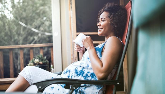 A pregnant woman relaxes with a cuppa